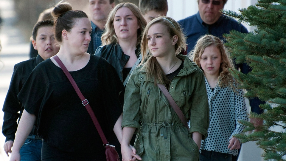 Holding hands, young mourners arrive at the funeral for Jordan Segura, one of the victims of an April 15 mass stabbing attack, in Calgary on Monday, April 21, 2014. (Larry MacDougal / THE CANADIAN PRESS)
