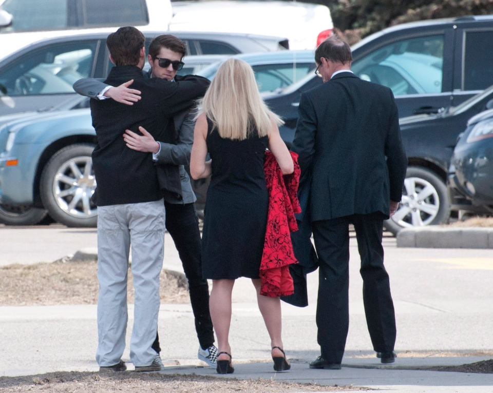 Mourners hug at the funeral for Jordan Segura, one of the victims of last week's mass stabbing attack in Calgary, on Monday, April 21, 2014. (Larry MacDougal / THE CANADIAN PRESS)