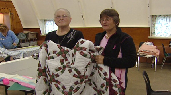 Barbara Grube, left, presents a quilt to Brenda Turcotte-Laberge, whose husband was killed in the Goderich tornado, in Auburn, Ont. on Thursday, Oct. 27, 2011.