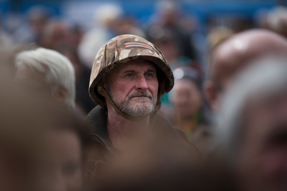 A pro-Russian activist wearing a helmet with St. George ribbon, which has become a symbol of the pro-Russian insurgency in eastern Ukraine, listens to a speaker as he and others gather at barricades at the Ukrainian regional office of the Security Service in Luhansk, Ukraine, Monday, April 21, 2014. (AP / Alexander Zemlianichenko)