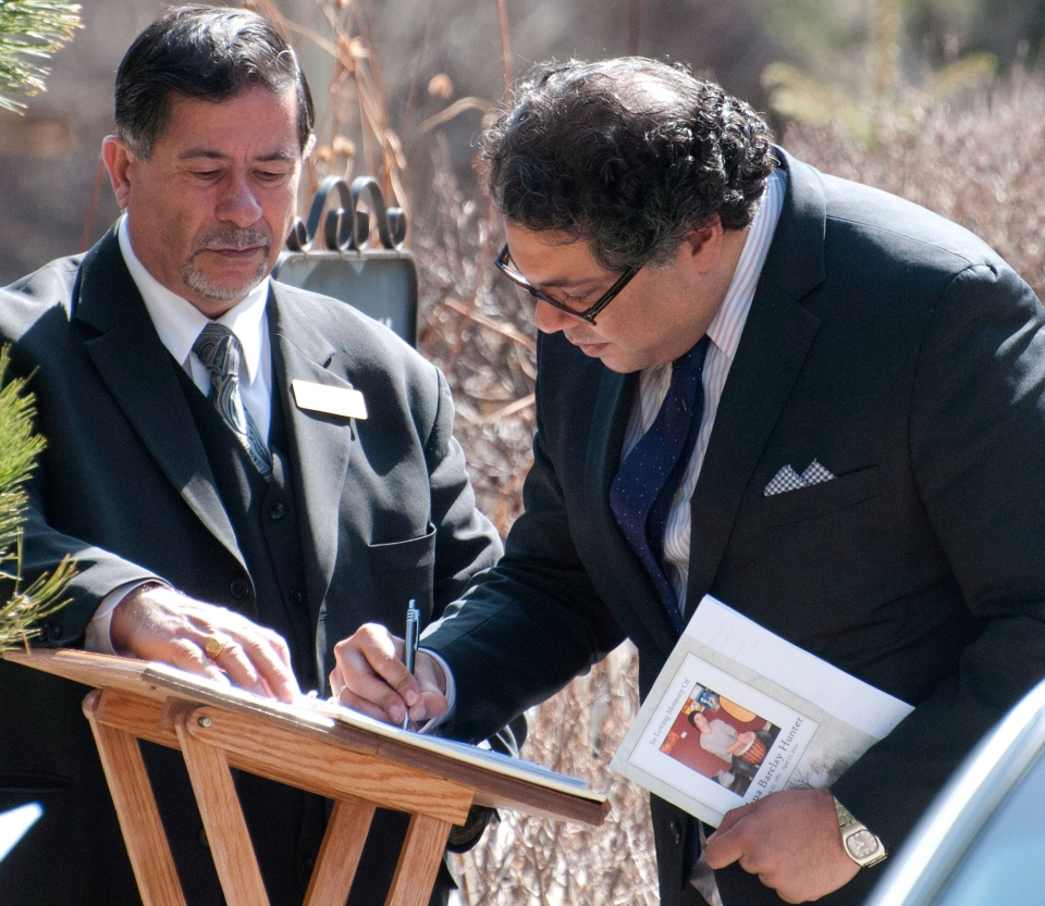 Calgary Mayor Naheed Nenshi, right, signs the guest book as he arrives at the funeral for Josh Hunter, victim of the April 15 mass stabbing, in Calgary, Alberta on Monday, April 21, 2014. (Larry MacDougal / THE CANADIAN PRESS)