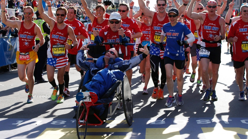 Dick Hoyt and Rick Hoyt, from Holland, Mass., cross the finish line surrounded by supporters in the 118th Boston Marathon, Monday, April 21, 2014 in Boston. The Hoyts have said this, their 32nd Boston Marathon, will be their last. (AP / Elise Amendola)