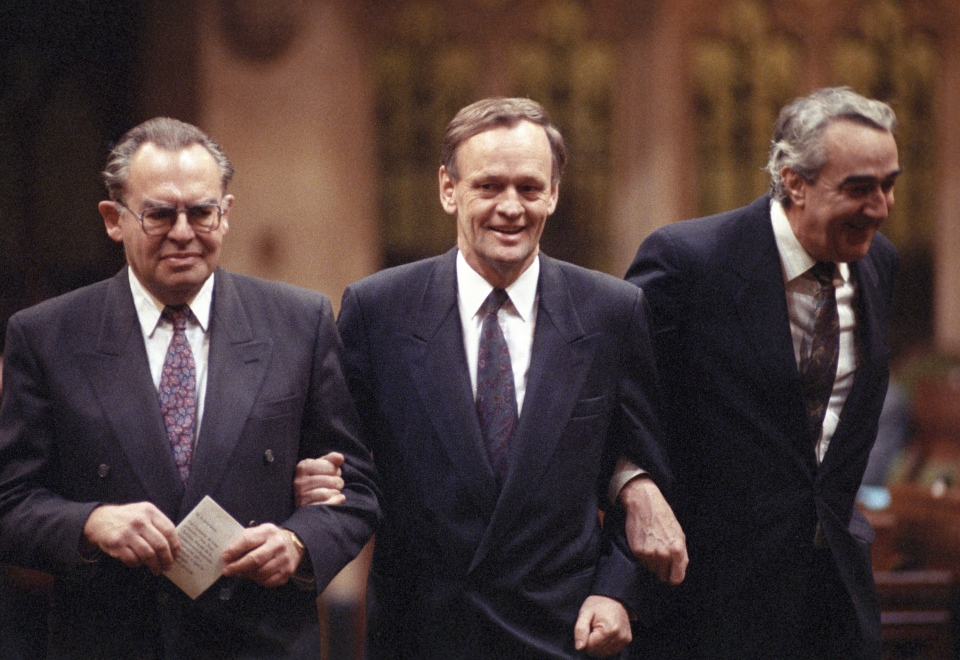 Then-Opposition Leader Jean Chretien is led to House of Commons Speaker John Fraser by Liberal MPs Herb Gray and Marcel Prud'Homme as he claims his House of Commons seat in Ottawa on Jan. 15, 1991. (Chuck Mitchel / THE CANADIAN PRESS)