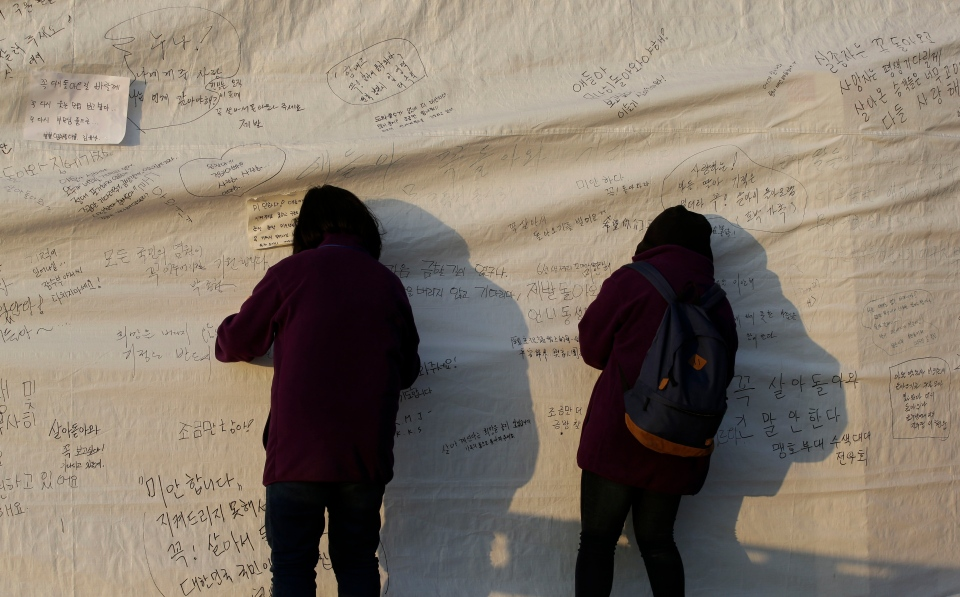 Visitors write messages on the side of a tent, wishing safe return of missing passengers aboard the sunken ferry Sewol at a port in Jindo, south of Seoul, South Korea, Tuesday, April 22, 2014. (AP / Lee Jin-man)