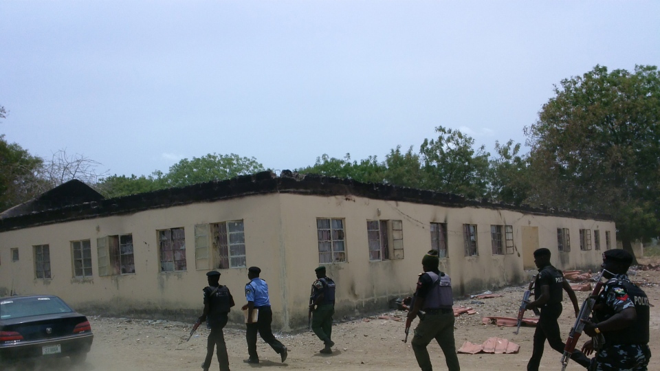 Security walk past burned government secondary school Chibok, were gunmen abducted more than 300 students in Chibok, Nigeria, Monday, April, 21. 2014. (AP / Haruna Umar)