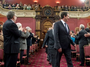 PQ MLA Pierre Karl Peladeau walks in with colleagues as Parti Quebecois elected members are sworn in at a ceremony on Tuesday, April 22, 2014 at the legislature in Quebec City. (Jacques Boissinot / THE CANADIAN PRESS)