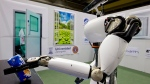 Amigo, a white robot the size of a person, uses information gathered by other robots to move towards a table to pick up a carton of milk and deliver it to an imaginary patient in a mock hospital room at the Technical University of Eindhoven, Netherlands, Wednesday Jan. 15, 2014. (AP / Peter Dejong)