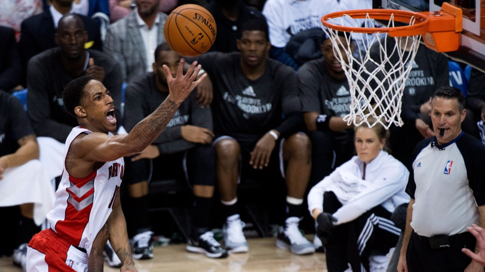 Toronto Raptors guard DeMar DeRozan, left, drive over Brooklyn Nets forward Andray Blatche, bottom, to score during second half NBA playoff basketball action in Toronto on Tuesday, April 22, 2014. (Nathan Denette / THE CANADIAN PRESS)