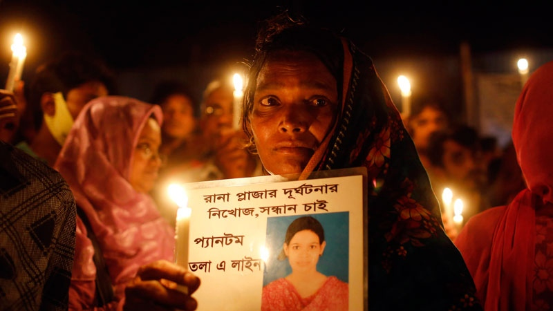 A Bangladeshi woman holds a candle with a portrait of a missing relative, victim of last year's Rana Plaza building collapse, during a gathering to pay tributes on the eve of the tragedy in Savar, near Dhaka, Bangladesh, Wednesday, April 23, 2014. (AP / A.M. Ahad)
