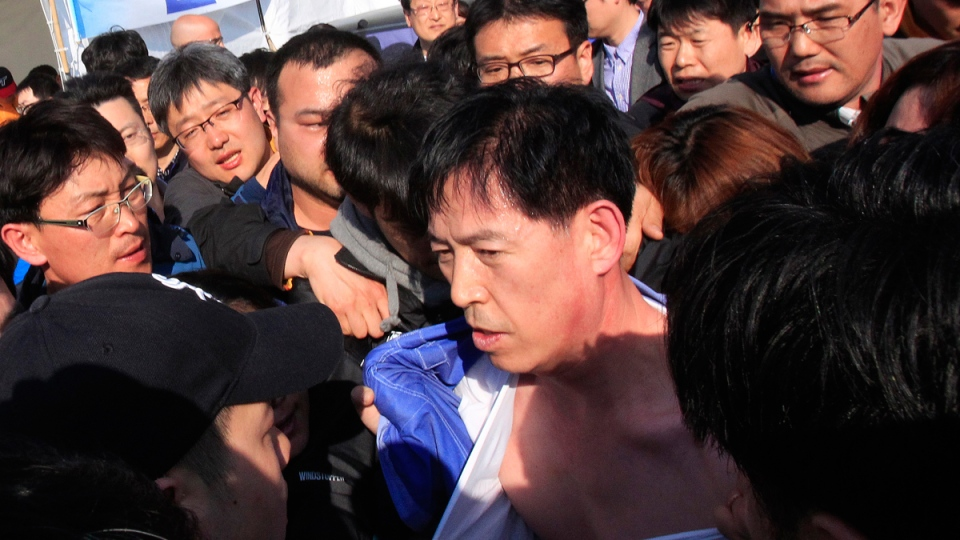 Choi Sang-hwan, South Korean Coast Guard police officer, is surrounded by relatives of passengers lost aboard the sunken ferry Sewol off Jindo, South Korea, Thursday, April 24, 2014. (AP / Ahn Young-joon)