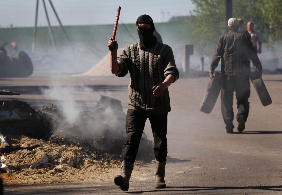 A pro-Russian masked militant directs traffic at a checkpoint following an attack by Ukrainian troops outside Slovyansk, Ukraine, Thursday, April 24, 2014. (AP / Sergei Grits)