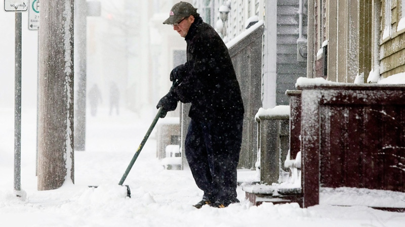 An unidentified man shovels his walk in Halifax on Sunday, Jan. 9, 2011. (Andrew Vaughan / THE CANADIAN PRESS)