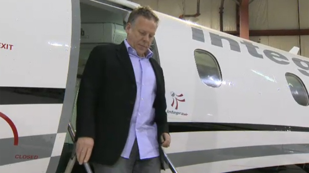 Roger Jewett, CEO of Jump On Flyaways, exits a plane in a Calgary hangar