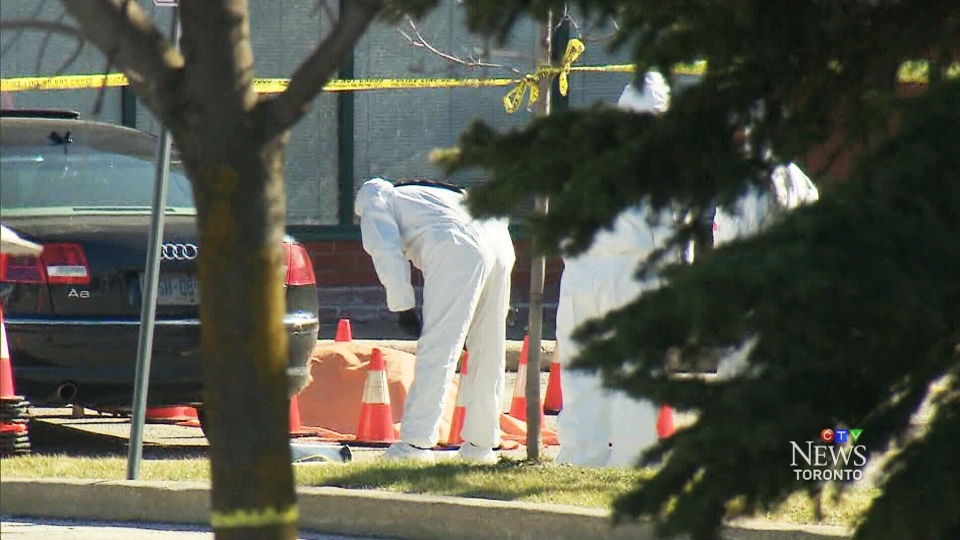Police investigators are visible in a strip mall parking lot after a man was fatally shot in Vaughan on Thursday, April 24, 2014.