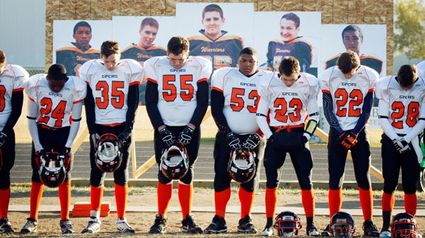 Portraits of four fallen and one injured teenager look over their teammates as the Grande Prairie Composite High School Warriors bow their heads during a moment of silence before the start of a semi-final playoff football game in Grande Prairie, Alta., Saturday, Oct. 29, 2011. (Jeff McIntosh / THE CANADIAN PRESS)