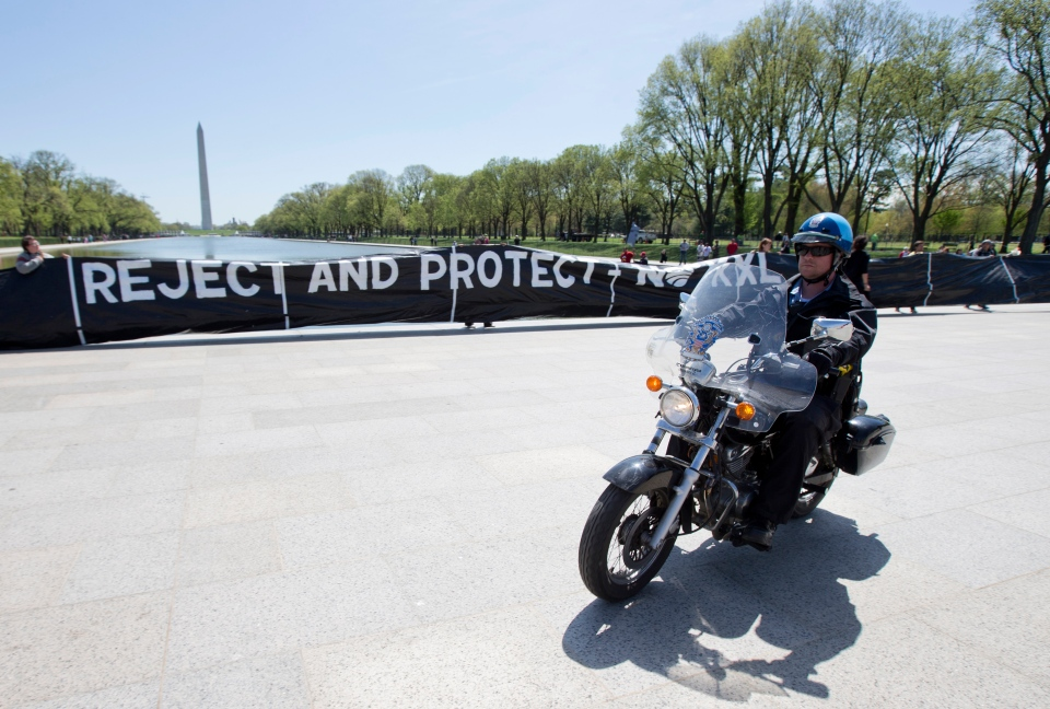 A U.S. Park Police officer rides his motorcycle near a group of of Native Americans, cowboys, ranchers and farmers, protesting the proposed Keystone XL oil pipeline, Thursday, April 24, 2014, on the National Mall in Washington. (AP / Manuel Balce Ceneta)