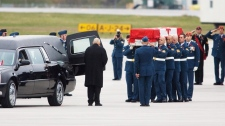 The remains of Sgt. Janick Gilbert, 34, is saluted by a group of veterans as it is loaded into a hearse at CFB Trenton en route to Ottawa on Saturday, Oct. 29, 2011. (Peter Redman / THE CANADIAN PRESS)