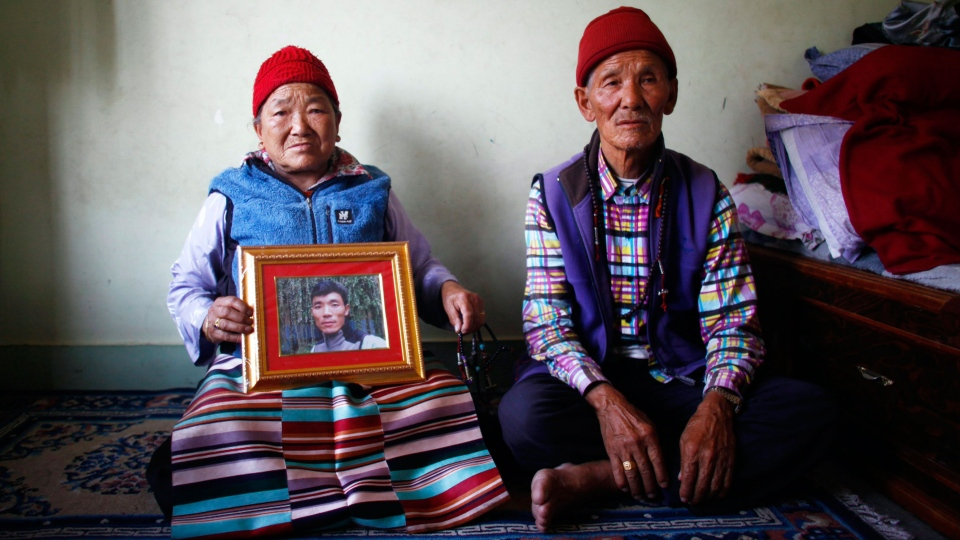Nimdige Sherpa holds a portrait of her son Ang Kaji Sherpa, killed in an avalanche on Mount Everest, with her husband Ankchu Sherpa seated beside her in their rented apartment in Katmandu, Nepal, Wednesday, April 23, 2014. (AP / Niranjan Shrestha)