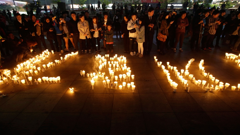 People stand near candles during a candlelight vigil for the safe return of passengers of the sunken ferry Sewol in Ansan, South Korea, Thursday, April 24, 2014. (AP / Lee Jin-man)