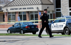Police remain on scene at Jonathan Law High School after a 16-year-old girl was stabbed to death in Milford, Conn., Friday, April 25, 2014. (The New Haven Register / Peter Hvizdak)