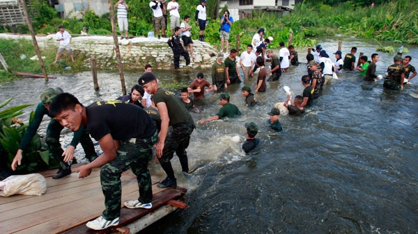 Thai soldiers use sandbags to fortify a broken flood barrier in Bangkok, Thailand, Sunday, Oct. 30, 2011. (AP / Apichart Weerawong)