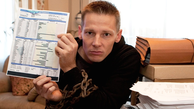 Former Canadian Forces soldier Pascal Lacoste holds a copy of a test that displays a high level of uranium in his system as he sits in his home in Quebec City, Wednesday, Oct. 26, 2011. (Jacques Boissinot / THE CANADIAN PRESS)
