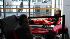 Stranded passengers rest on cots inside at Bradley International Airport, a day after a snowstorm in Windsor Locks, Conn., Sunday, Oct. 30, 2011. (AP / Jessica Hill)