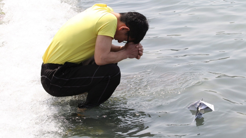 A relative of a passenger aboard the sunken ferry Sewol in the water off the southern coast, prays after releasing a paper boat with messages to wish for safe return of his missing loved one written to it, at a port in Jindo, South Korea, Friday, April 25, 2014. (AP / Ahn Young-joon)