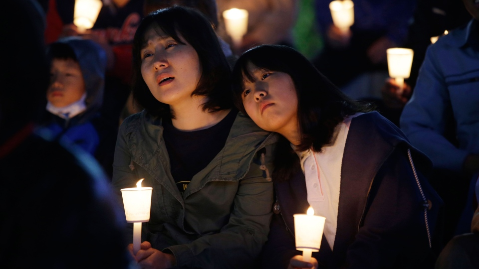 People react as they watch news report off of a computer screen during candlelight vigil for safe return of passengers of the sunken ferry Sewol in Ansan, South Korea, Friday, April 25, 2014.  (AP / Lee Jin-man)