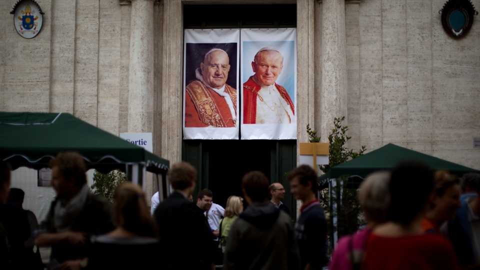 Worshipers gather in front of one of the entrances of the Saint Luigi dei Francesi (St. Louis of the French) church decorated with portraits of late Pope John Paul II and John XXIII during a mass in Rome, Saturday, April 26, 2014. (AP / Emilio Morenatti)
