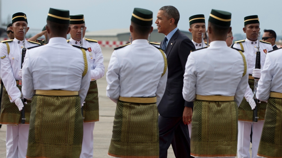 President Barack Obama walks between members of an honor guard as he arrives on Air Force One at the Royal Malaysian Air Force Airbase, Subang, outside of Kuala Lumpur, Malaysia, Saturday, April 26, 2014. (AP / Carolyn Kaster)