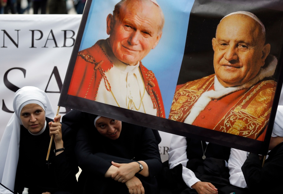 Nuns hold up pictures of late Pope John Paul II, top left, and Pope John XXIII, in St. Peter's Square at the Vatican, Saturday, April 26, 2014. (AP / Alessandra Tarantino)