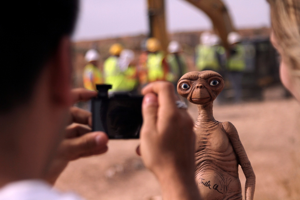 A man takes a photo of an E.T. doll in Alamogordo, N.M, Saturday, April 26, 2014. (AP / Juan Carlos Llorca)