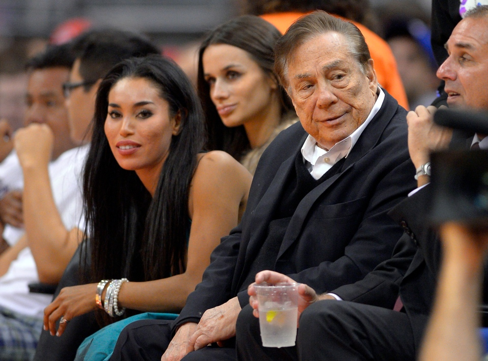 In this photo taken on Friday, Oct. 25, 2013, Los Angeles Clippers owner Donald Sterling, right, and V. Stiviano, left, watch the Clippers play the Sacramento Kings during the first half of an NBA basketball game in Los Angeles. (AP/Mark J. Terrill)