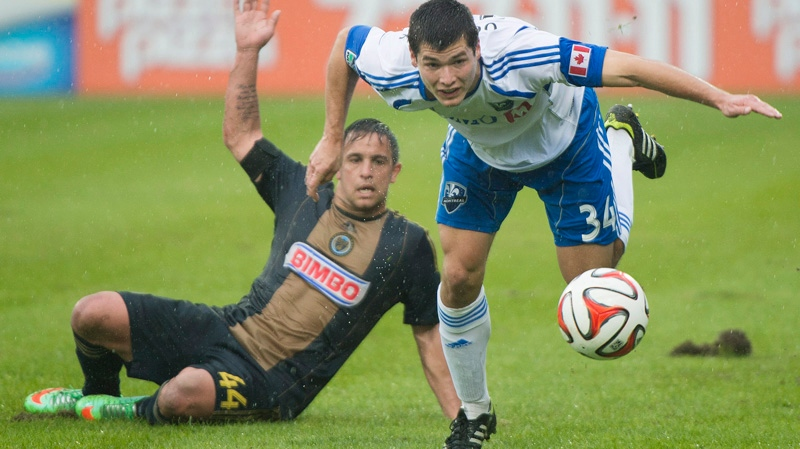 Montreal Impact's Karl Ouimette, right, is brought down by Philadelphia Union's Danny Cruz during first half MLS soccer action in Montreal, Saturday, April 26, 2014. THE CANADIAN PRESS/Graham Hughes