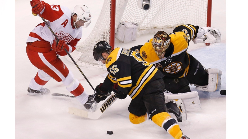 Boston Bruins' Tuukka Rask (40) and Johnny Boychuk (55) try to clear the puck away from Detroit Red Wings' Pavel Datsyuk (13) during the third period in Game 5 in the first round of the NHL hockey Stanley Cup playoffs in Boston, Saturday, April 26, 2014. Boston won 4-2 and eliminated the Red Wings from the playoffs. (AP Photo/Michael Dwyer)