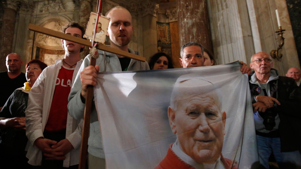Polish pilgrims hold a flag portraying Pope John Paul II during a vigil prayer in the Sant'Agnese in Agone church in piazza Navona, Rome, Saturday, April 26, 2014. (AP / Riccardo De Luca)