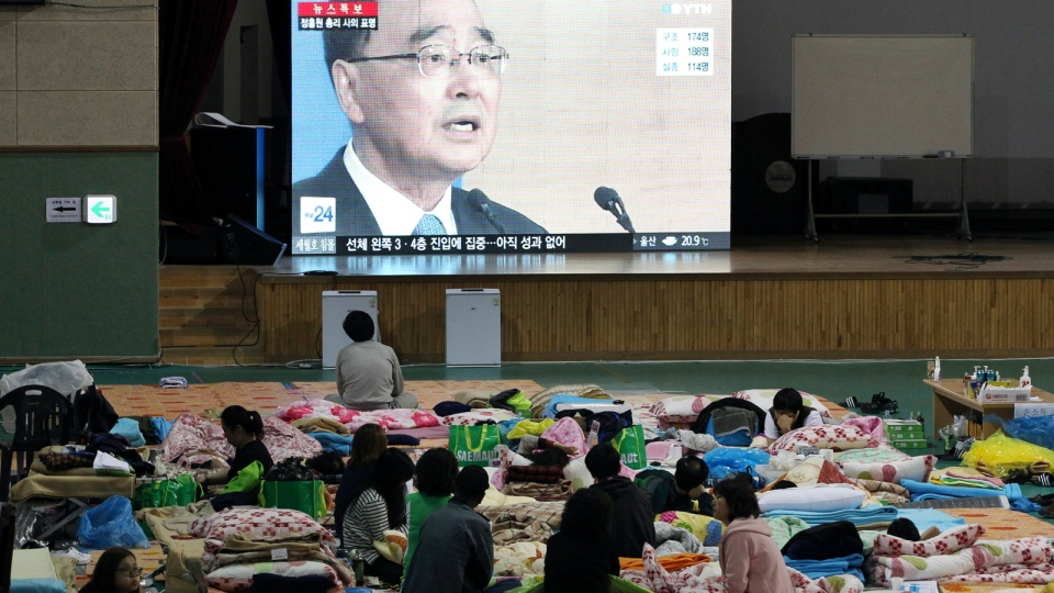 Relatives of passengers aboard the sunken ferry Sewol watch a television news program showing South Korean Prime Minister Chung Hong-won speaks at a press conference after offering his resignation, at a gymnasium in Jindo, South Korea, Sunday, April 27, 2014. (AP / Ahn Young-joon)