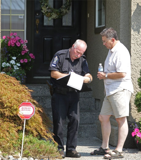 A wildlife conservation officer, left, speaks with a friend of a woman who was attacked by a bear outside her home in Coquitlam, B.C., on Wednesday Aug. 6, 2008. (Darryl Dyck   THE CANADIAN PRESS)