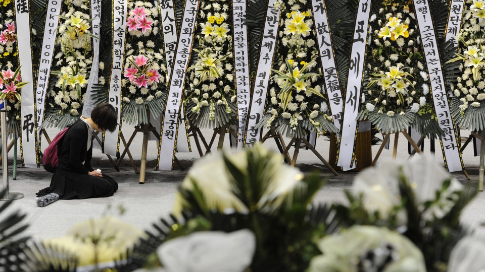A mourner pays tribute to the victims of the sunken ferry Sewol near condolence flowers at a temporary memorial altar in Ansan, south of Seoul, South Korea, Monday, April 28, 2014. (AP / Yonhap)