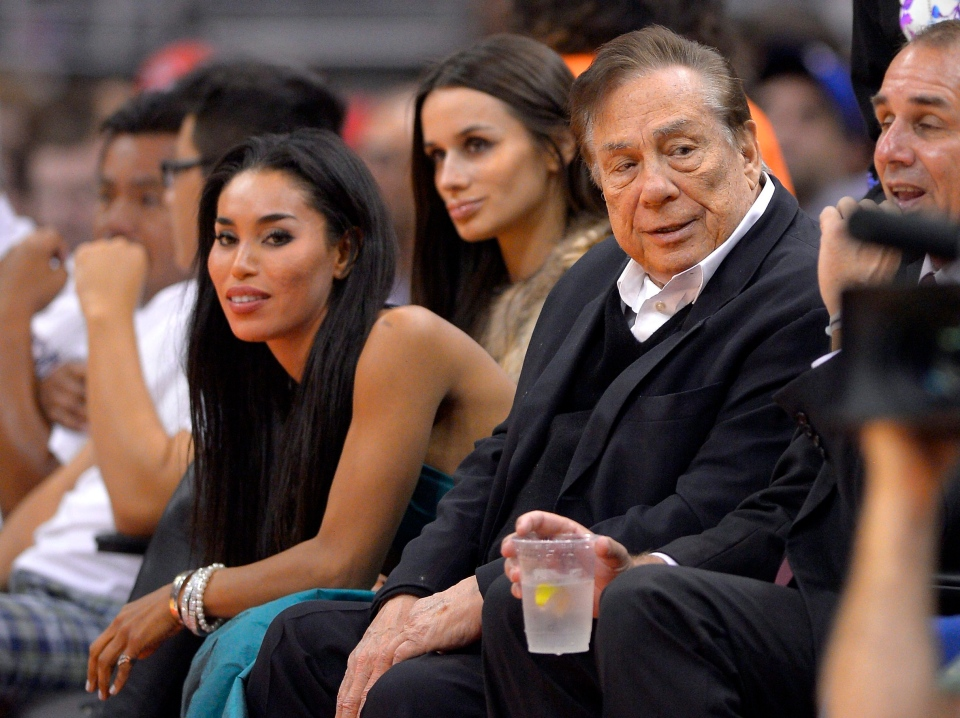 Los Angeles Clippers owner Donald Sterling, right, and V. Stiviano, left, watch the Clippers play the Sacramento Kings during the first half of an NBA basketball game in Los Angeles, Friday, Oct. 25, 2013. (AP / Mark J. Terrill)