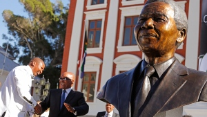 South African President Jacob Zuma, second left, talks with Mandla Mandela, left, after they and other dignitaries unveiled a bust of former South African President Nelson Mandela, right, at the South African Parliament in Cape Town, South Africa, Monday, April 28, 2014. (AP / Schalk van Zuydam)
