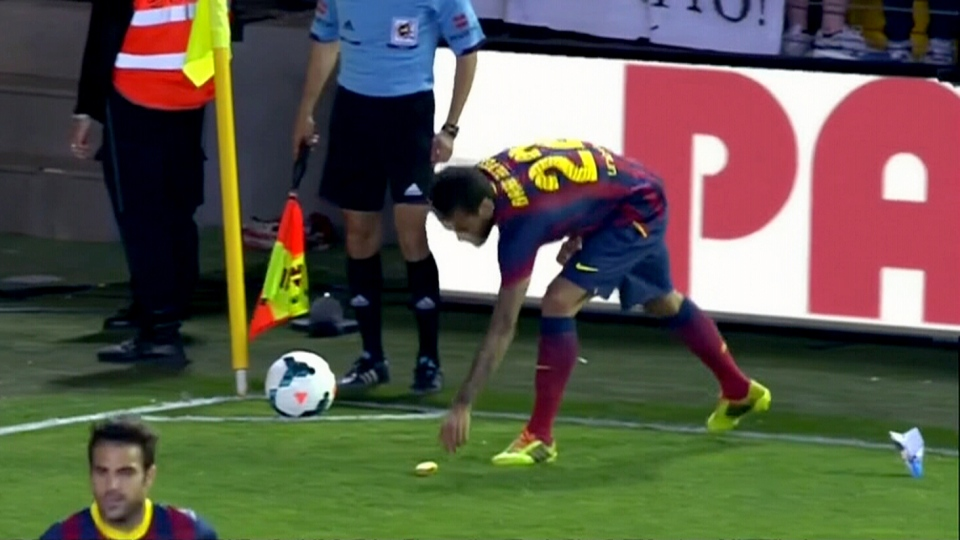 Barcelona defender Dani Alves picks up a banana during a game.