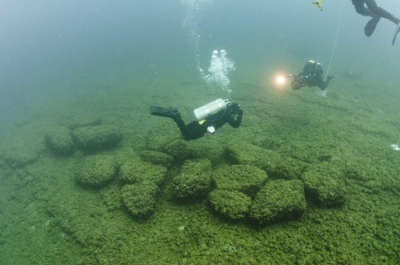 Divers examine boulders on the bottom of Lake Huron near Alpena, Mich., that were used as caribou drive lanes by prehistoric hunters in this June 13, 2011 file photo, provided by Thunder Bay National Marine Sanctuary via the University of Michigan News Service. (Thunder Bay National Marine Sanctuary / University of Michigan News Service / Tane Casserly)