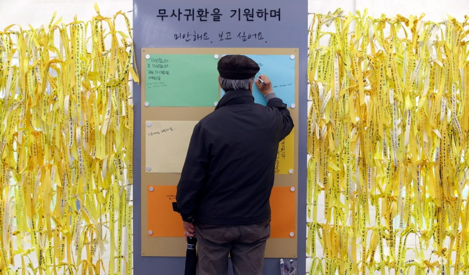A man writes a message on the board near yellow ribbons as signs for cherishing the memory of deceased persons and hope for safe return of missing passengers aboard the sunken ferry boat Sewol in the water off the southern coast, at a group memorial altar in front of the City Hall in Seoul, South Korea, Monday, April 28, 2014. (AP / Lee Jin-man)
