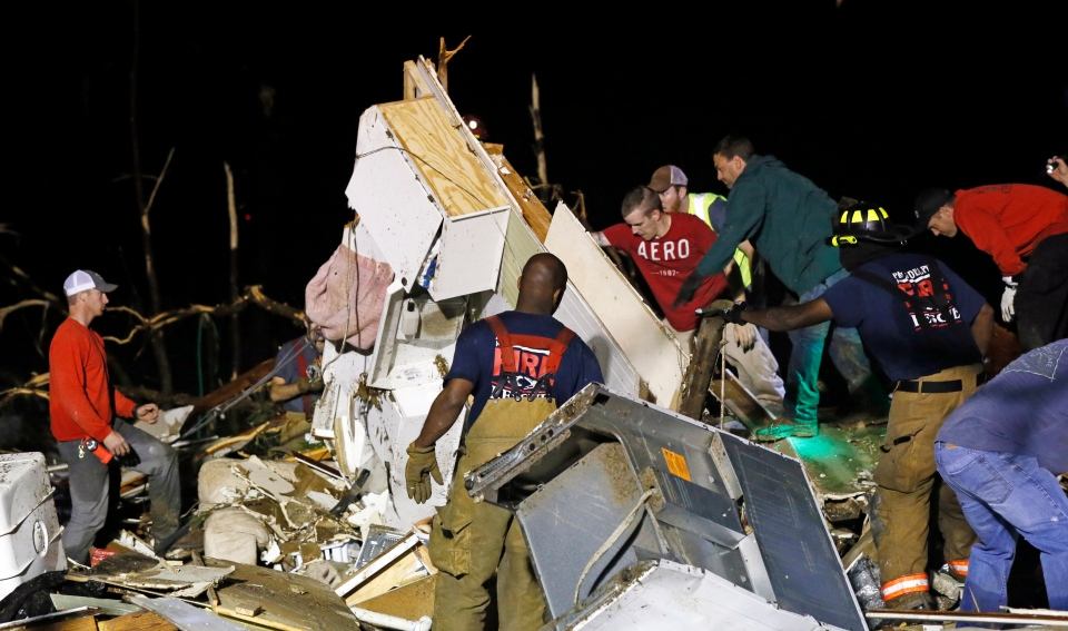 Emergency personnel search the remains of several mobile homes for survivors in Louisville, Miss., early Tuesday, April 29, 2014. (AP / Rogelio V. Solis)