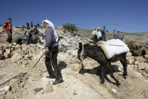 A Palestinian man pulls a donkey over the rubble of a house after it was demolished by the Israeli army in the West Bank city of Khirbet al-Tawil, south of Nablus, Tuesday, April 29, 2014. (AP / Nasser Ishtayeh)