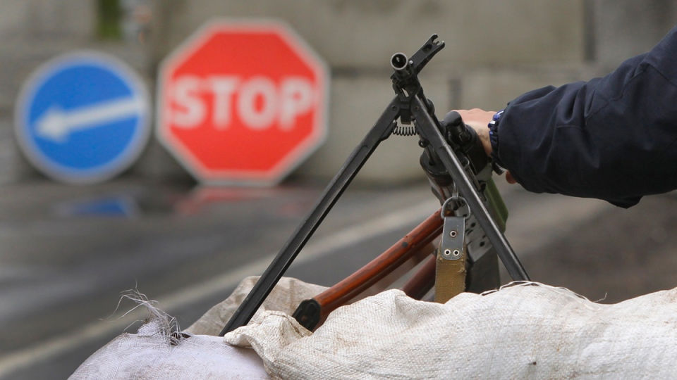 Ukrainian government soldier holds his machine gun as he guards a checkpoint near the village of Dolina, 30 kilometres from Slovyansk, eastern Ukraine, Tuesday, April 29, 2014. (AP / Sergei Grits)