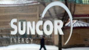 A pedestrian is reflected in a Suncor Energy sign in Calgary, on Feb. 1, 2010. (Jeff McIntosh / THE CANADIAN PRESS)