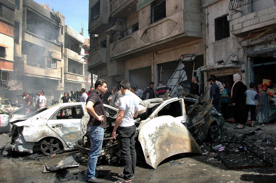 In this photo released by the Syrian official news agency SANA, Syrian people gather at the site of one of two car bombs that exploded in the pro-government district of Zahra in the central Syrian city of Homs, Syria, Tuesday, April 29, 2014. (SANA)